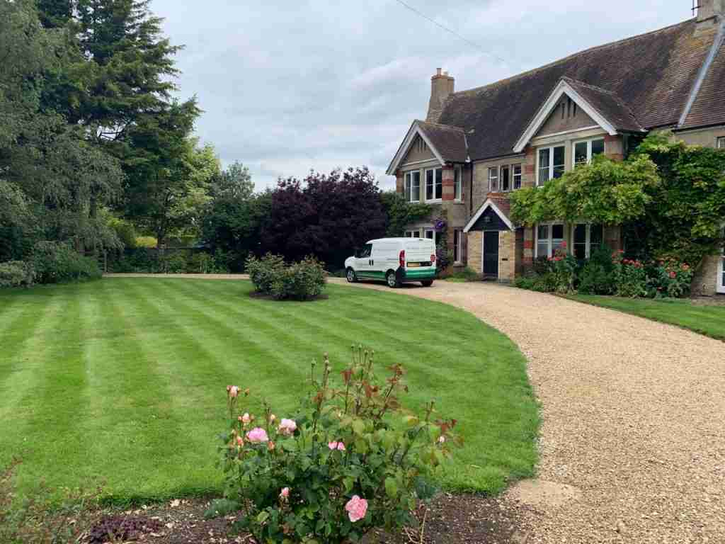 a picturesque cottage with a green lawn and a van in front